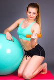 Beautiful blonde woman doing exercises with dumbbells on fitness. Ball over gray background Royalty Free Stock Photos
