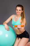 Beautiful blonde woman doing exercises with dumbbells on fitness. Ball over gray background Stock Photos