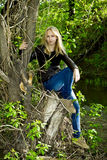 Beautiful blonde woman on dried-up tree Stock Photography