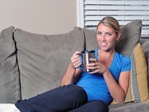 Beautiful blonde woman drinking coffee on couch Royalty Free Stock Image