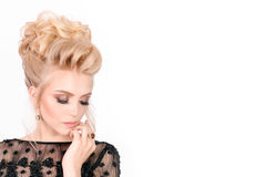 Beautiful blonde woman in elegant black evening dress with updo hairstyle. Her eyes is closed showing bright makeup Stock Photography