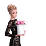 Beautiful blonde woman in elegant black evening dress with updo hairstyle holding a giftbox, bouquet of flowers in her Stock Photography