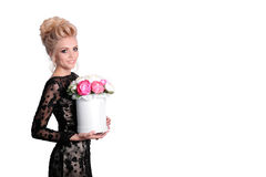 Beautiful blonde woman in elegant black evening dress with updo hairstyle holding a giftbox, bouquet of flowers in her Royalty Free Stock Images