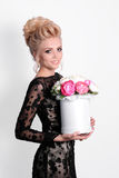 Beautiful blonde woman in elegant black evening dress with updo hairstyle holding a giftbox, bouquet of flowers in her Royalty Free Stock Photo