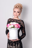 Beautiful blonde woman in elegant black evening dress with updo hairstyle holding a giftbox, bouquet of flowers in her Stock Photo