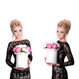 Beautiful blonde woman in elegant black evening dress with updo hairstyle holding a giftbox, bouquet of flowers in her Royalty Free Stock Photos
