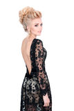 Beautiful blonde woman in elegant black evening dress with updo hairstyle. Lady looking over her shoulder on white Royalty Free Stock Photos