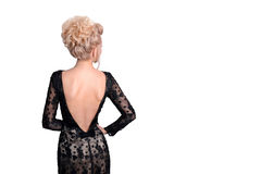 Beautiful blonde woman in elegant black evening low cut back dress with updo hairstyle. Lady looking over her shoulder Royalty Free Stock Image