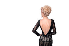 Beautiful blonde woman in elegant black evening low cut back dress with updo hairstyle. Lady looking over her shoulder Stock Image