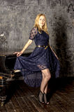 Beautiful blonde woman in an elegant dress at the piano in a dark room Stock Image