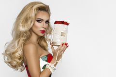 Beautiful blonde woman in an elegant evening gown with red roses, holding a Valentine`s gift, a flowerbox with flowers. Beauty stock photo