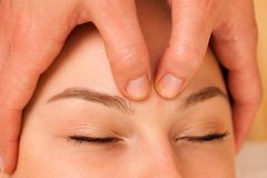 Beautiful blonde woman having a face massage in spa salon. Beautiful blonde woman enyoing massage treatment in sap salon Royalty Free Stock Photo