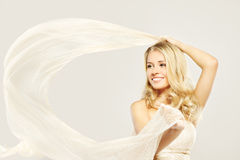 Beautiful blonde woman with fabric. Happy beautiful blonde woman carefree dancing with white flying fabric stock images
