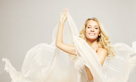 Beautiful blonde woman with fabric. Happy beautiful blonde woman with long hairs, carefree dancing with white flying fabric royalty free stock photos