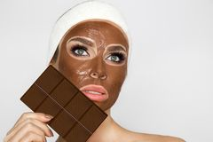 Beautiful blonde woman with a facial mask, beauty spa.Chocolate face mask. Beautiful blonde sexy woman model with a facial mask, beauty spa.Chocolate face mask Stock Images