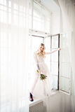 Beautiful Blonde Woman Fiancee with Bridal Hairstyle. Beautiful Young Blonde Fiancee with Bridal Hairstyle, Event Makeup and Flowers Opening the Window. Fashion Royalty Free Stock Image