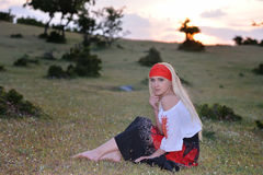 Beautiful blonde woman on field at sunset, summer evening Stock Image