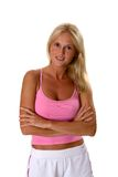 Beautiful blonde woman in fitness clothes arms folded. Beautiful blonde woman in fitness clothes standing with arms folded on a white background stock photo