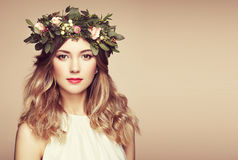 Beautiful blonde woman with flower wreath on her head. Beauty girl with flowers hairstyle. Perfect makeup. Beauty fashion. Spring woman Stock Images