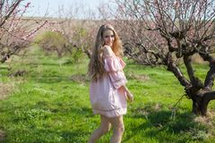 Beautiful blonde woman in a flowered Peach Garden in spring with pink flowers royalty free stock photography