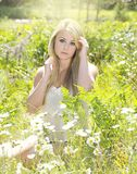 Beautiful blonde woman in flowers. Young blonde woman in flower meadow Royalty Free Stock Image