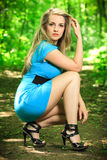 Beautiful blonde woman on a forest road. Beautiful blonde woman in blue dress posing on a forest road, in nature, fashion photography Royalty Free Stock Photos