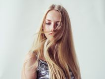 Beautiful blonde woman girl with long blond hair smooth and beau. Ty in silver wear. Studio shot stock photography