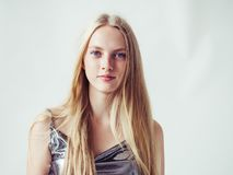 Beautiful blonde woman girl with long blond hair smooth and beau. Ty in silver wear. Studio shot stock photo