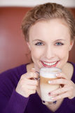 Beautiful blonde woman with glass of latte macciato Royalty Free Stock Images