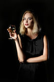 Beautiful blonde woman with glass of white wine on black background Royalty Free Stock Images