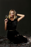 Beautiful blonde woman with glass of white wine on black background Stock Images