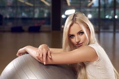 Beautiful blonde woman with gray exercise ball. Half body portrait of beautiful woman with long blonde hair and blue eyes dressed in white t-shirt sitting in Royalty Free Stock Images