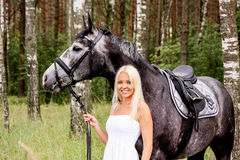 Beautiful blonde woman and gray horse in forest Royalty Free Stock Photos