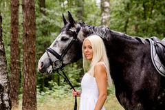 Beautiful blonde woman and gray horse in forest Royalty Free Stock Photo