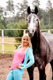 Beautiful blonde woman and gray horse in forest Royalty Free Stock Images