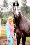 Beautiful blonde woman and gray horse in forest Royalty Free Stock Photography