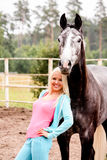 Beautiful blonde woman and gray horse in forest Stock Photo