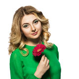 Beautiful blonde woman in a green dress that looks at the camera while holding  flower on isolate white background. Royalty Free Stock Images