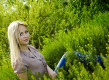 Beautiful blonde woman  in green grass Stock Images