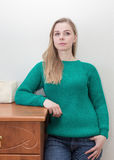 Beautiful blonde woman in green pullover royalty free stock images