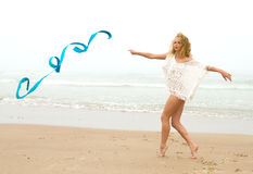 Beautiful blonde woman gymnast working out with ribbon on the b Royalty Free Stock Photography