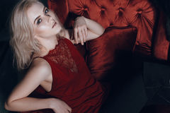 Beautiful blonde woman with hair and make-up sitting in a red chair Stock Photography