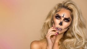 Beautiful blonde woman in Halloween makeup and beautiful hair on a beige background in the studio. Skeleton, monster and witch. royalty free stock image