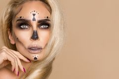 Beautiful blonde woman in Halloween makeup and beautiful hair on a beige background in the studio. Skeleton, monster and witch. royalty free stock photo