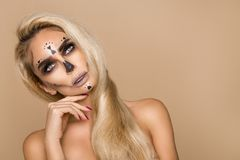 Beautiful blonde woman in Halloween makeup and beautiful hair on a beige background in the studio. Skeleton, monster and witch. royalty free stock photos