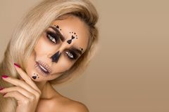 Beautiful blonde woman in Halloween makeup and beautiful hair on a beige background in the studio. Skeleton, monster and witch. stock photo