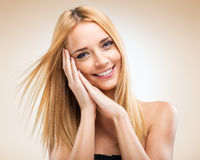 Beautiful blonde woman with hands in the face of Royalty Free Stock Image