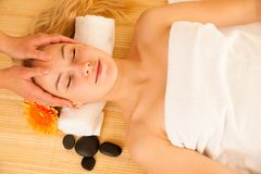 Beautiful blonde woman having a face massage in spa salon Stock Photos
