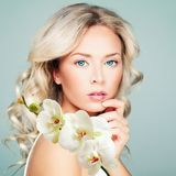Beautiful blonde woman with healthy skin, wavy hair. And white orchid flowers. Facial treatment, cosmetology, beauty, skin care and spa royalty free stock photo