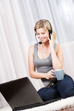 Beautiful blonde woman in her apartment over the internet. Royalty Free Stock Images